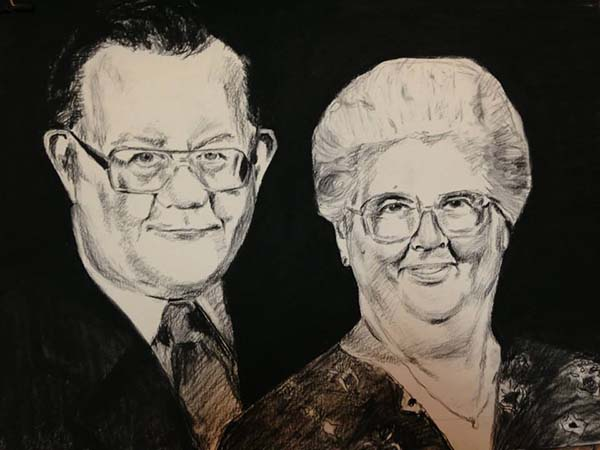 Traditional charcoal portrait drawing of an older couple. Both are wearing glasses, the man is wearing a black suit with a tie and the women is wearing a floral shirt. The background is black.