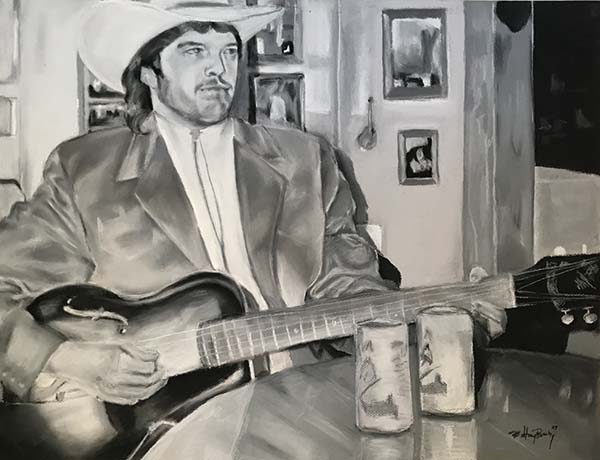 Black and white drawing in chalk pastel of a man (musician) with a cowboy hat on sitting at a table playing the guitar. In the background there is a wall with framed photographs giving the viewer the idea that the musician is sitting in a home.